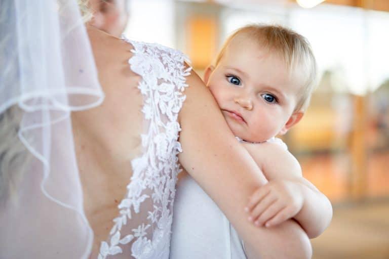 bébé dans les bras de la mariée regarde objectif